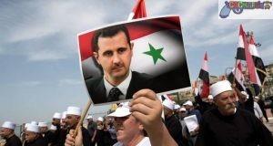 Varias personas pertenecientes a la minoría religiosa de los drusos ondean banderas sirias y sostienen fotografías del presidente sirio, Bachar Al Assad, para celebrar el 72º aniversario del Día de la Independencia siria, en la localidad drusa de Ein Qiniya, en los Altos del Golán (Israel), el 17 de abril de 2018. (EFE/ Atef Safadi)